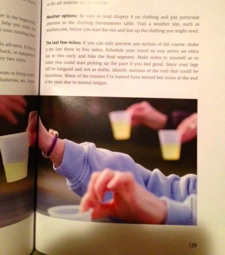 From this photo on page 139 of Galloway's book on trail running, you can expect volunteers to hold out lots of plastic cups for you to drink from and toss in the road when you're done!