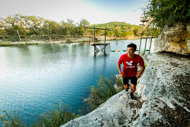 A camper running along the Nueces, with part of the obstacle course in the background.